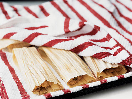 Place tamales, seam sides down, on the rack of a broiler pan lined with a damp towel; cover. Cook as directed in recipe below.