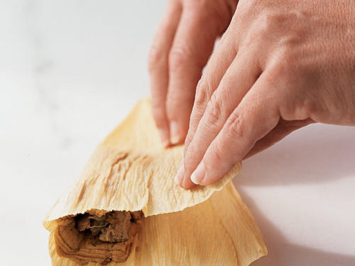 Fold corn husk over, covering filling with dough.