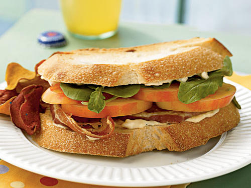 Update your lunch routine with this new spin on the classic BLT. Mr. Stripey tomatoes are a variety of heirlooms with pale, yellow skins with a pinkish-orange blush, occasionally with green stripes. Substitute a beefsteak or other large, firm tomato. Pancetta is Italian cured bacon that gets cooked in the oven (no splattering on the cook-top). Substitute regular cured bacon, if desired. Prepare the mayonnaise mixture and cook the pancetta up to one day ahead.