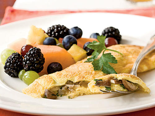 Use a mix of seasonal varieties or your favorite mushrooms to fill this classic French-style omelet. If your pan becomes too hot and the eggs begin to set too quickly, simply lift the pan off the heat to slow the cooking as you stir. Garnish with fresh flat-leaf parsley sprigs for a pretty presentation, and serve with fresh fruit.