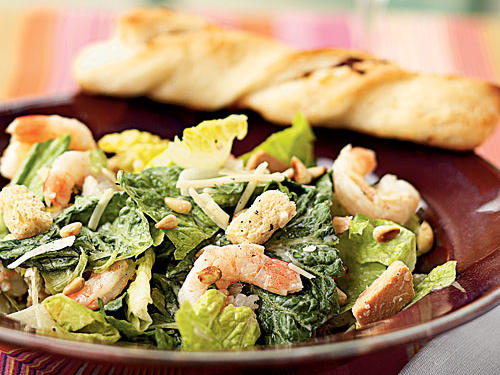 Top romaine lettuce with grated Parmesan cheese, pine nuts, shrimp, croutons, and a homemade Caesar dressing for a satisfying main-dish salad.