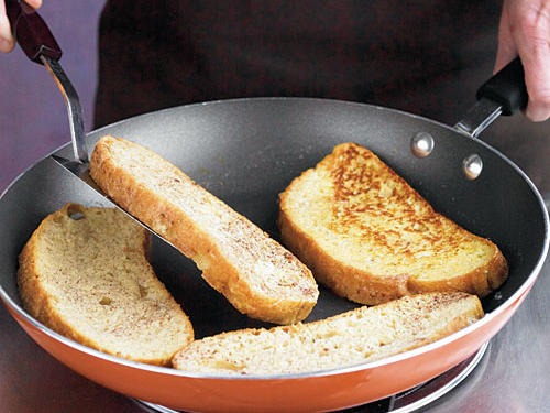 Cook 2 minutes on each side or until bread is lightly browned. Remove from pan, and drizzle with syrup.