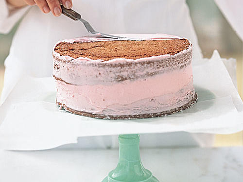 Place an unfrosted layer bottom-side up on the frosted layer. Apply a thin layer of frosting (known as a crumb coat) to the entire cake to seal in any loose crumbs. Allow it to set in the refrigerator for about 15 minutes.