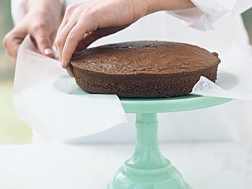 Unwrap the cake layers, and place 1 layer on a cake stand. Slip strips of wax paper beneath the edges to keep the stand clean.
