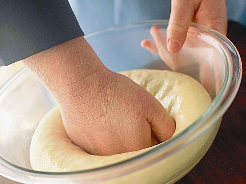 Punch the dough down by pressing into the center with a closed fist. Let the dough rest for 5 minutes (this rest period makes the dough easier to handle), and then shape it into the desired form (rolls, loaves, etc.) for the final rise. Place the shaped dough on a baking sheet or in a pan. Coat the dough lightly with cooking spray, and cover it (just as you did for the first rise). The rising procedure and checking for doneness are the same as for the first rise. Then bake the bread according to the recipe's directions.