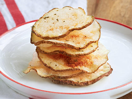 Cut 1 large unpeeled baking potato into 1/8-inch-thick slices. Arrange one-third of potato slices on a large microwave-safe plate. Coat potatoes with cooking spray; sprinkle with 1/2 teaspoon ranch dressing mix. Microwave, uncovered, at HIGH 4 minutes. Turn potato slices over. Microwave at HIGH 3 to 4 minutes or until dried and beginning to brown. Remove from plate; cool on wire racks. Repeat procedure with remaining potato slices and dressing mix.SERVES 6 (serving size: about 10 chips)CALORIES 52; FAT 0.2g (sat 0g); SODIUM 71mg