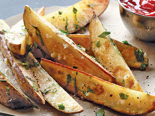 These roasted potato wedges, blistered and brown from the heat of the oven, beautifully combine the rich flavors of potato and garlic.
