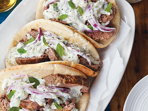 A Greek specialty, gyros are traditionally made from spiced, spit-roasted lamb. Here, we mold a ground lamb mixture into loaves. The yogurt dressing is a variation on traditional tzatziki.