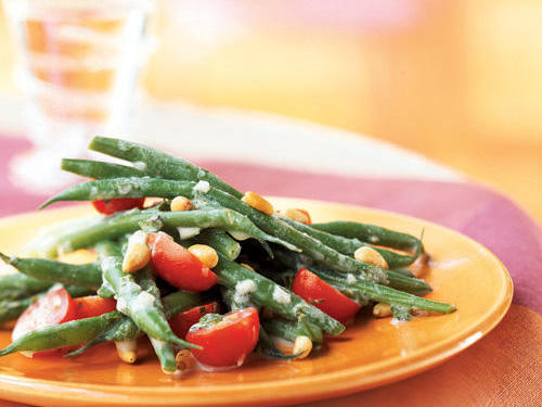 Green beans, basil, shallots, tomatoes, and pine nuts are tossed with a dressing that's simultaneously creamy and light for a versatile dish.