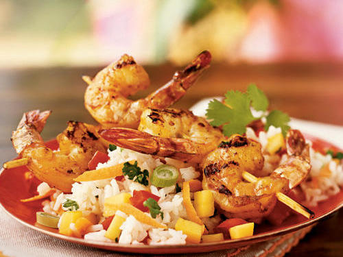 Marinating the shrimp in curry, ginger, and garlic before grilling gives them a spicy flavor that complements the tangy-sweet mango and richly flavored coconut rice on which they're served.