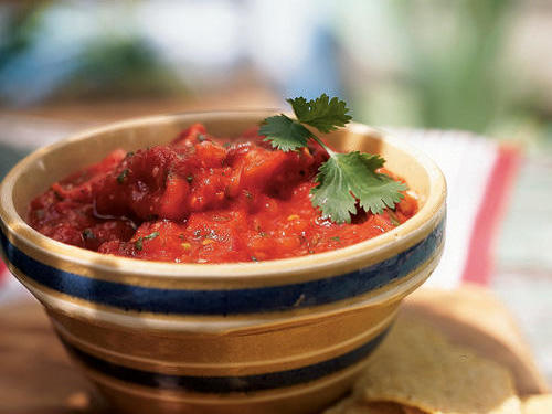 Smoked tomatoes and jalapeño pepper make a world of difference in this salsa and blend beautifully with the garlic and lime. Garnish with a cilantro sprig, if desired.
