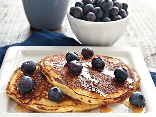 These tender blueberry pancakes are simple enough for weekday mornings yet tremendously crowd-pleasing for weekend entertaining. For maximum flavor and a burst of blueberry in every bite, use deep-blue, plump berries for mixing into the batter and sprinkling over top.
