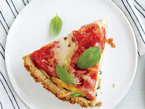 This crust, made tender and flaky with heart-healthy olive oil, makes the perfect base for farm-fresh tomatoes and earthy-sweet basil. For a less expensive alternative to pine nuts, substitute toasted sunflower seeds.