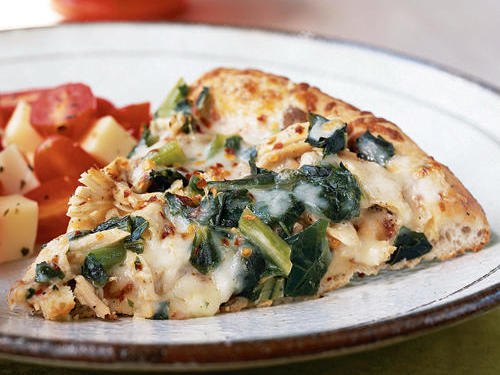 Collard greens and leftover turkey meld beautifully with commercial Alfredo sauce and nutty fontina cheese, resulting in an easy yet inventive meal. Rubbing the pizza crust with a halved garlic clove imparts lots of flavor with little effort and no chopping.