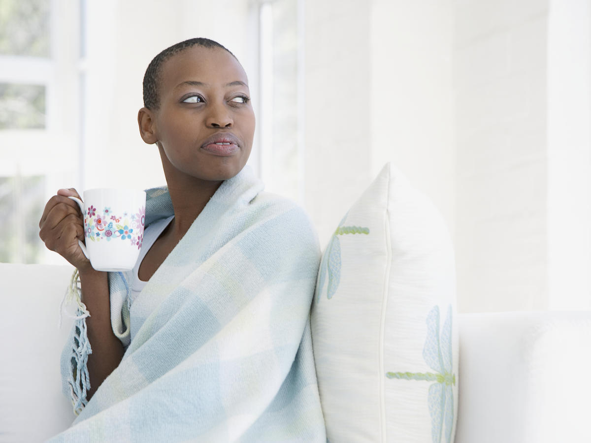 Sick woman on couch in blanket with cup of tea