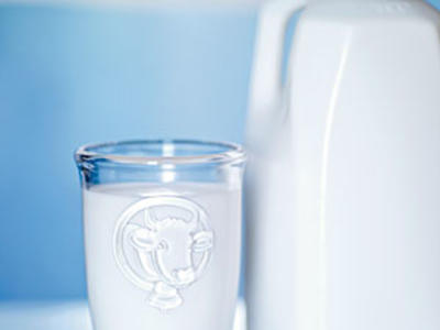 A glass of milk next to a milk jug