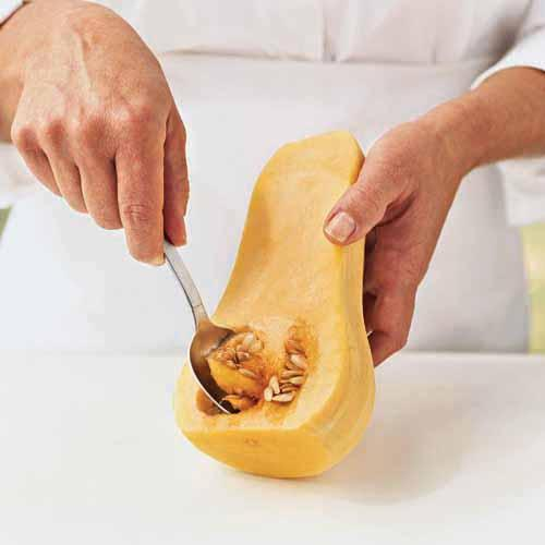Scooping the seeds from a butternut squash