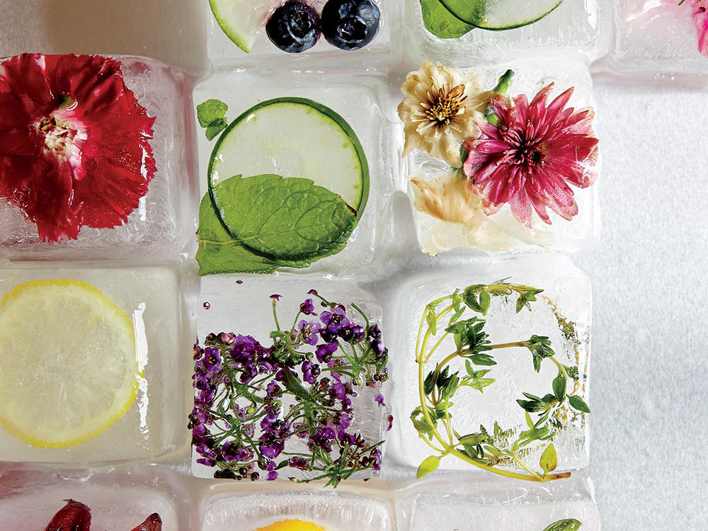 Looking for a pretty cool way to dress up summertime drinks? Try our technique for taking plain ice cubes from everyday to extraordinary simply by studding them with fresh fruits, vegetables, herbs, and flowers. These striking blocks bring a pop of color and a hint of flavor to cocktails, punch, lemonade, or even plain water. It's a simple make-ahead process; using boiled, filtered water is key to crystal clear cubes. All else is up to your tastes. Mix and match by pairing ingredients like cucumber and mint to chill down a mojito, herbal thyme ice for lemonade, or purple pepper flowers for a spicy gin and tonic. Whether you're having a few friends over for a casual patio supper or hosting a more formal affair, these ice cubes add a graceful touch to any festive setting.
