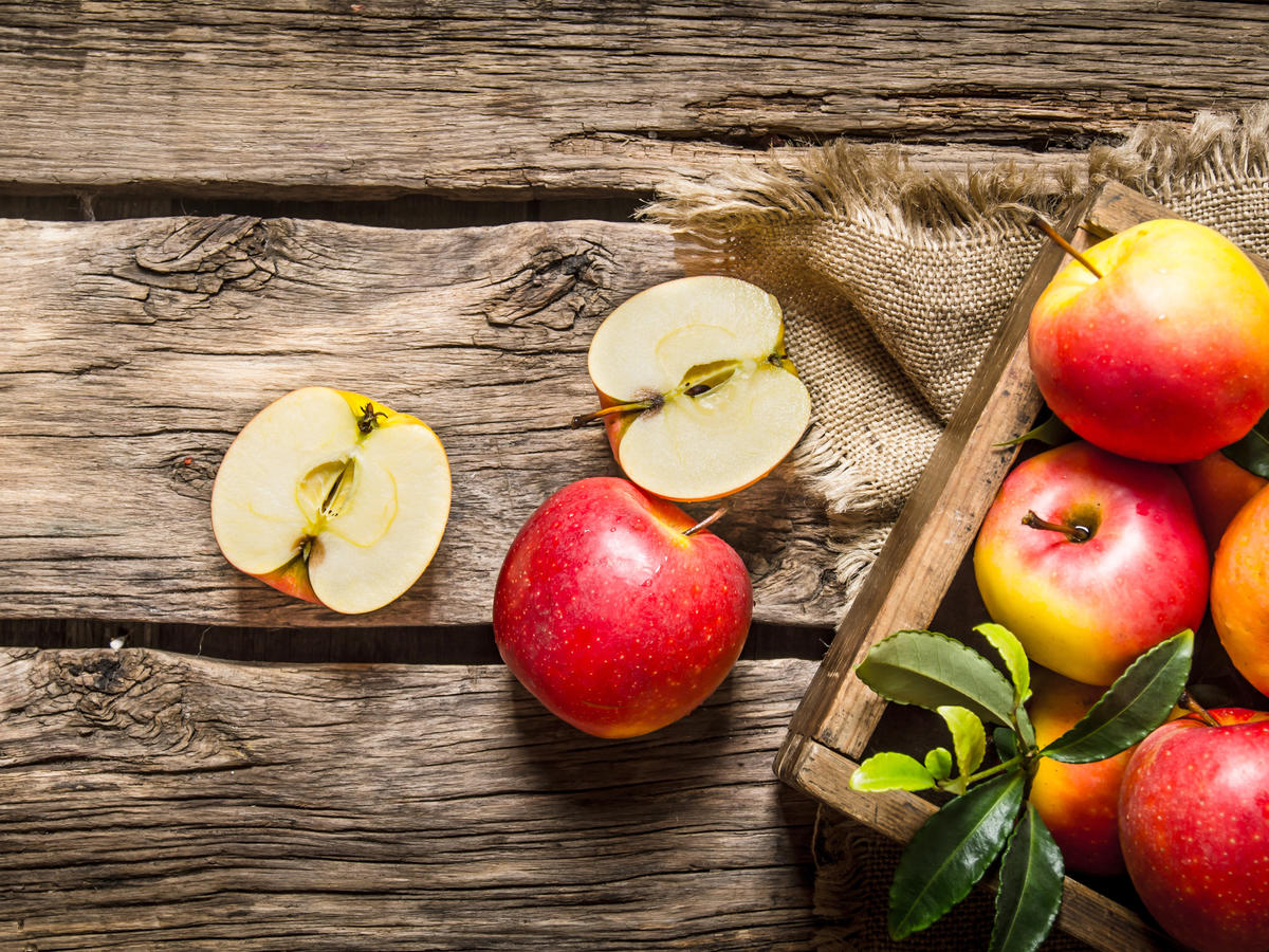 Fresh red apples in wooden box.  On wooden background. Top view