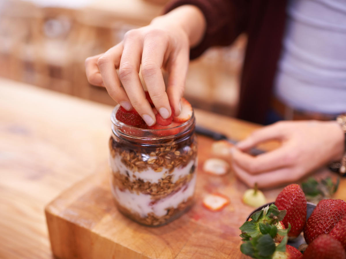 1610w-getty-woman-adding-strawberries-yogurt-granola.jpg