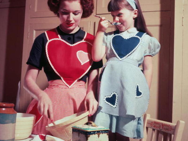 circa 1955:  A young girl helps in the kitchen, while her mother bakes a cake.  (Photo by Hulton Archive/Getty Images)