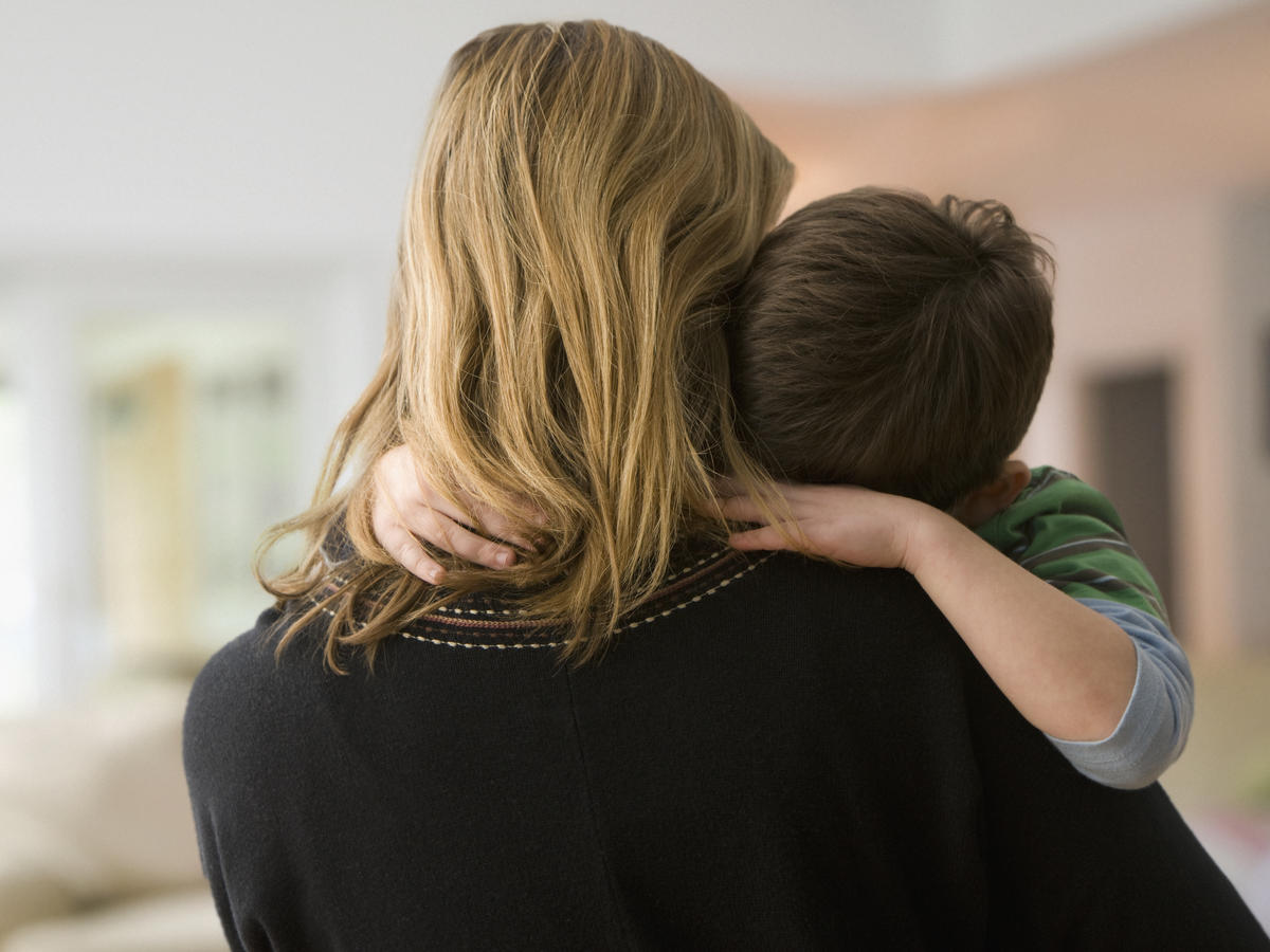 Mother carrying sick son to doctor