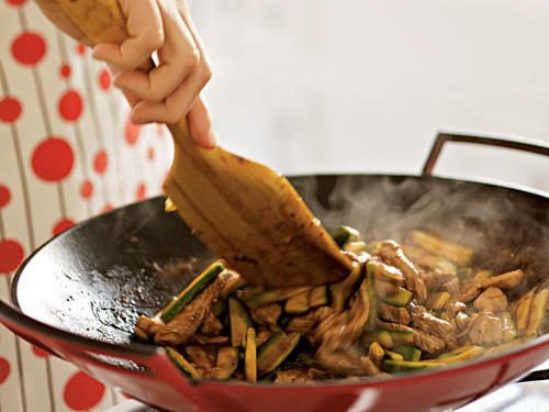 Chicken and vegetables stir-frying in a red wok